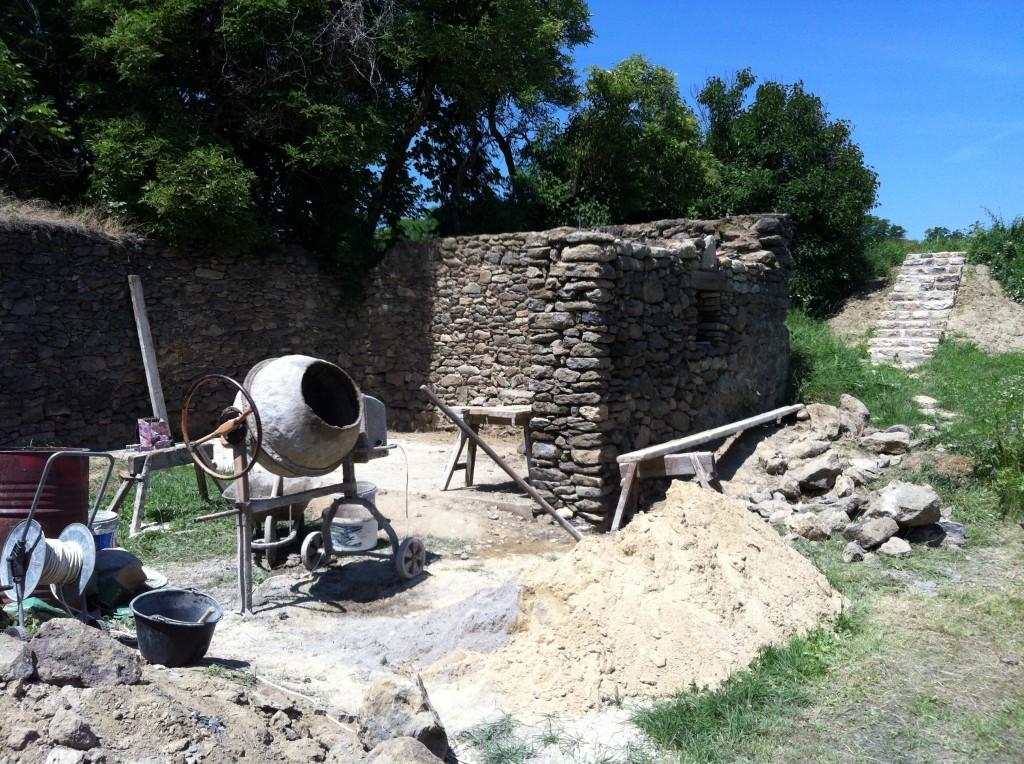 Itt a kőfal már egyenletes magasságúra visszaszedve, a visszabontott fal újra falazva, benne a kis ablaknyílással.