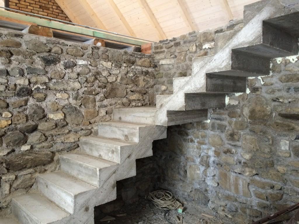 Íme a látszó beton lépcső. A galériás lakrészben ezen lehet felmenni a galériára, ahonnan a levendula kertre nyílik majd a francia erkélyes ajtó :) A lépcsőt felpolírozzuk és festeni fogjuk. Piszkos szürkére, vagy fehérre, még meglátom. Vas korlátot fog kapni. De nem díszes kovácsoltvasat, hanem minimál jellegű vas korlátot. Ahol látszik a tető, ott még kőfalat kell rakni, mert ez a lépcső végig a kőfal mellett vezet felfelé.