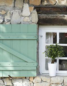 A ház udvar felőli ablakai szintén provence kék spalettákat kapnak, de fehér keret nélkül, látszó fa áthidalóval. Nagyon megfogott a fa áthidalók hangulata :)